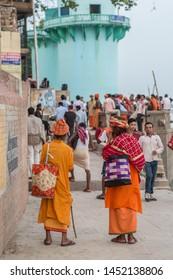 Varanasi / India - July 15 2019: Two sadhus, hindu devotees, walking riverside in the holy city of Varanasi on a afternoon