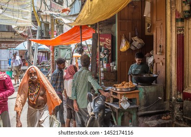 Varanasi / India - July 15 2019: A street vendor selling food in an alley in the holy city of Varanasi on a hot summer afternoon.