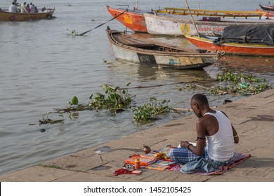 Varanasi / India - July 16 2019: A Hindu man praying by the Ganga river in the holy city on a early morning.