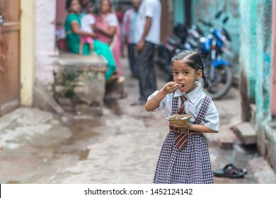 Varanasi / India - July 16 2019: A schoolgirl eating Idly, a traditional Indian snack, as her breakfast before school in a small street in Varanasi