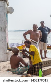 Varanasi / India - July 16 2019: A man getting the traditional shaving of hair before swimming in the holy river Ganges on a hot summer morning