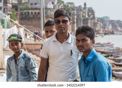 Varanasi / India - July 16 2019: A group of indian guys posing in front of the Ganga river on a hot summer day.
