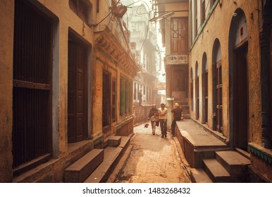 VARANASI, INDIA: Local people walking on narrow streets with tall houses in historical indian city on January 4, 2019. Varanasi urban agglomeration had population of 1,435,113
