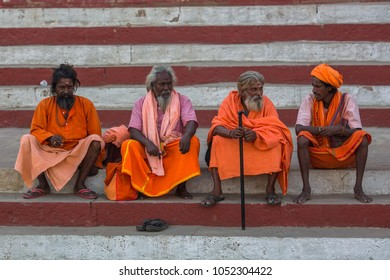 VARANASI, INDIA - MAR 17, 2018: Group of Sadhu (holy men) on the ghats of Ganga river. Varanasi is most important pilgrimage sites in India, one of the 7 sacred cities of Hinduism.