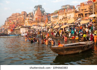 VARANASI, INDIA - MAR 22, 2018: Pilgrims plunge into the water holy Ganges river in the early morning. According to legends, the city was founded by God Shiva about 5000 years ago.