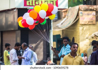 VARANASI, INDIA - MAR 25, 2018: Indian seller of balloons near the holy Ganges river. According to legends, Varanasi city was founded by God Shiva about 5000 years ago.
