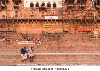 VARANASI, INDIA - MARCH 03, 2015. Two old hindu men stepping the stairs beside the carved walls of ancient fortress in Varanasi. Authentic Indian architecture. Morning, near The Ganges river.