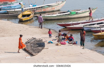 Varanasi, India - March 12, 2017: People and colourful boats at the bank of river Ganges in Varanasi city the holy town of India