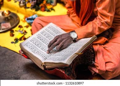 VARANASI, INDIA - MARCH 18, 2017: Old sadhu hand wearing hand watch pointing at line of holy book Varanasi, India.