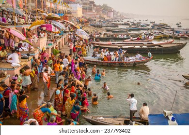 VARANASI, INDIA - MARCH 21, 2013: Boats and people on the ghats on the banks of Ganges river in holy city of Varanasi on March 21, 2013 in Varanasi, Uttar Pradesh, India.