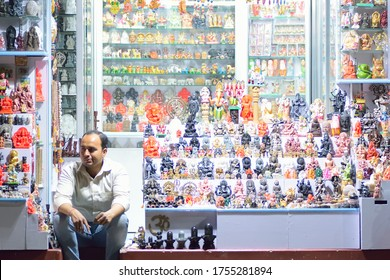 Varanasi, India - March 9, 2019 : Indian small shop owner selling Idols & items for religious offering in Varanasi, India. Local small businesses depend of tourism for their livelihood