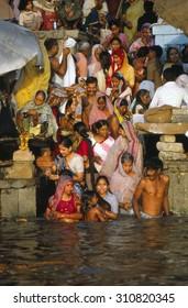 VARANASI, INDIA - NOV 1976 - Hindu pilgrims bathe in the Ganges River at dawn, Varanasi ( Benares), India