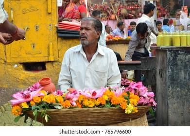 Varanasi, India - November 1, 2017:  A flower vendor sitting with his flowers near a Hindu temple.