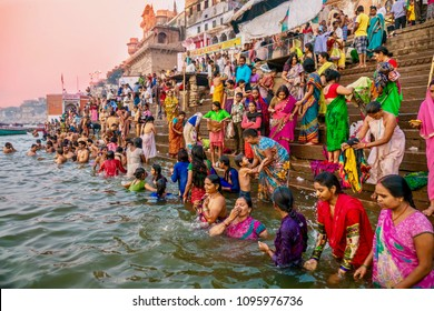 Varanasi, India - November 11, 2015. Showing the colorful traditional clothing and Hindu religious ritual of bathing in the Ganges River from the ancient ghats of Varanasi.