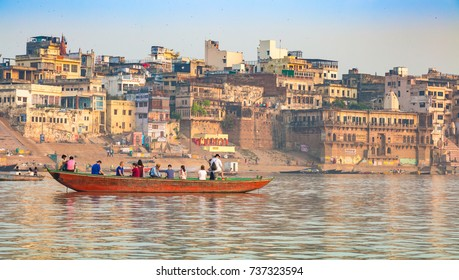 Varanasi, India, October 12, 2017: Tourists enjoy a boat ride on the holy Ganges river overlooking the ancient architectural buildings and temples of Varanasi, India.