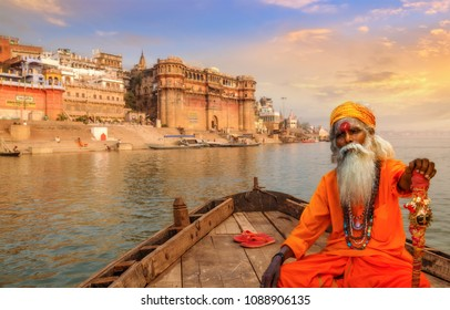 Varanasi, India, October 12,2017: Sadhu baba on a wooden boat overlooking the historic Varanasi city and Ganges river ghats, India.