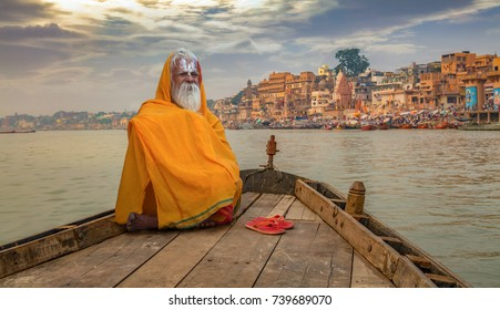 Varanasi, India, October 12,2017: Sadhu baba in meditation on a wooden boat overlooking the historic Varanasi city and Ganges river ghats, India.