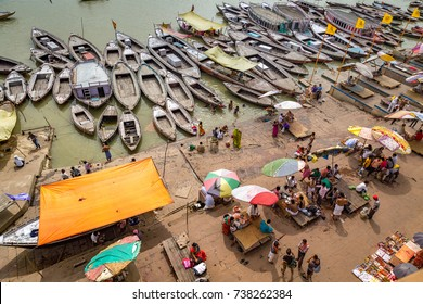 Varanasi, India, October 13,2017: Varanasi ghat aerial view of multicolored wooden boats lined up at the Ganges river ghat with tourists and vendors.