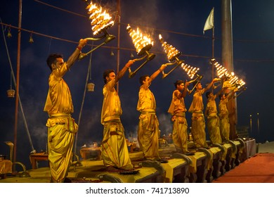 Varanasi, India, October 13,2017: Young priests perform the holy Ganga aarti ceremony rituals with holy fire at dawn at the Ganges river bank at Varanasi, India.