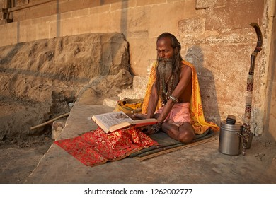 Varanasi, India, October 2011. A Sadhu reads a holy book in a ghat on the Ganges River.