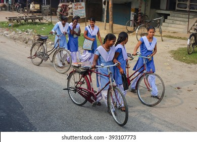 VARANASI, INDIA - OCTOBER 28: School girls going their homes from city to village, on bicycles, - popular indian transport, - October 28, Varanasi, India