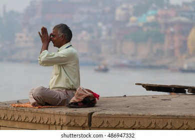 VARANASI, INDIA - OCTOBER 29, 2013: Morning prayer by the ghat along the Ganga river at Varanasi, India.