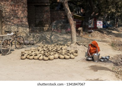 Varanasi, India-January 19, 2019: Traditionally dressed young Indian woman washes the metal pots and dishes in the street of a village near Varanasi.