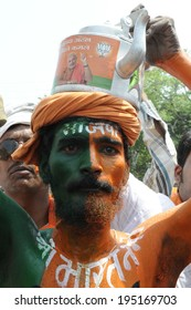 VARANASI - MAY 8:  A BJP supporter chanting slogans while being face painted in BJP colour and with a kettle on his head on May 8, 2014 in Varanasi , India.
