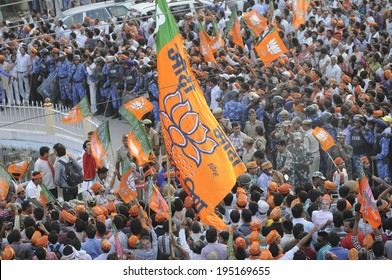 VARANASI - MAY 8:  Supporters waiving BJP party flags during a roadshow in front of BHU university on May 8, 2014 in Varanasi , India.
