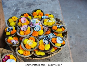 Varanasi, Uttar Pradesh - 20.04.2019: A basket full of oil lamps adorned by marigold flowers on sell for floating on the ganges as prayer in the ghats of Varanasi after ganga arti.
