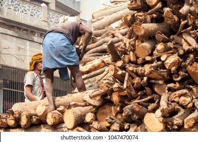 VARANASI, UTTAR PRADESH / INDIA - FEBRUARY 1 2006: Two men stacking trees to stunk for cremation.