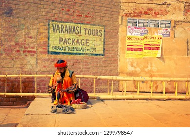 VARANASI, UTTAR PRADESH / INDIA - JANUARY 8, 2019: Fakir plaing with cobra on stone steps of ghats of Kashi