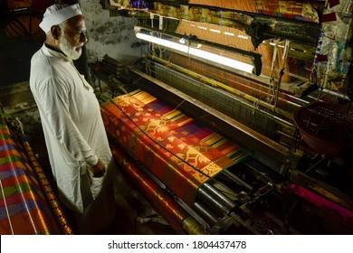 VARANASI, UTTAR PRADESH, INDIA -MAY 12 2019-A WEAVER (BUNKAR)  IN VARANASI MAKING WORLD FAMOUS BANARASI SARI ON HIS HANDLOOM WEAVING MACHINE