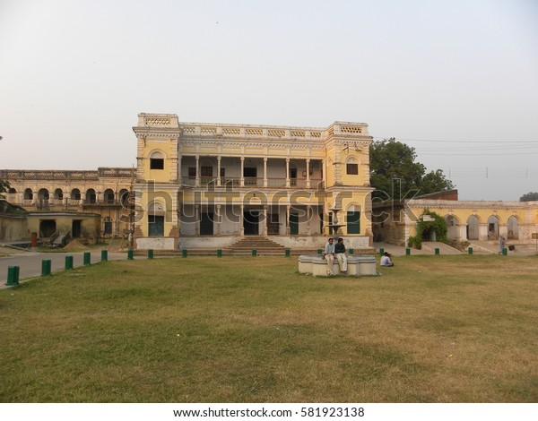 Varanasi, Uttar Pradesh, India - Nov 1, 2009 Old Ramnagar fort with people, green grass, fields, plants and green sky