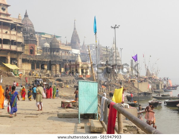Varanasi, Uttar Pradesh, India - Nov 2, 2009 Landscape view of Manikarnika Ghat with fire wood, funeral smoke and fire, cremation grounds, temple, people and river Ganga