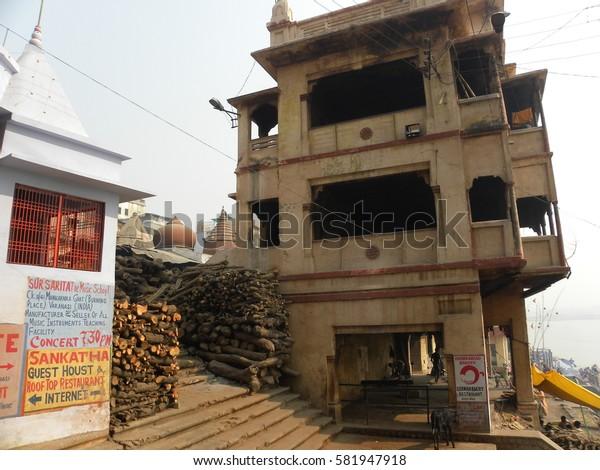 Varanasi, Uttar Pradesh, India - Nov 2, 2009 Old tall buildings, firewood and temple at Manikarnika Ghat