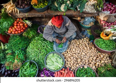 VARANASI, UTTAR PRADESH/INDIA - 8 JANUARY 2014.  A man surrounded by vegetables and greens at his place at Indian Bazaar. A mix of colors and textures. Captured in India, Uttar Pradesh, Varanasi.