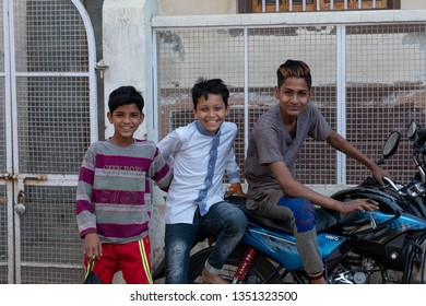 Varanasi, Uttar Pradesh/India - March 20,2019: A group of boys pose for a photo on a parked motorbike on Holika.