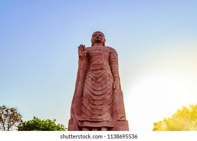 Varanasi,India- April-2018: The 80 feet high standing statue of Lord Buddha made of sandstone at Sarnath in Varanasi Uttar Pradesh India.