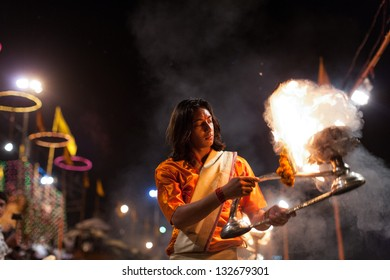 VARANASI,INDIA - MARCH 6:An unidentified Hindu priest performs religious ceremony(fire puja) at Dashashwamedh Ghat on March 6, 2010 in Varanasi,Uttar Pradesh,Central India