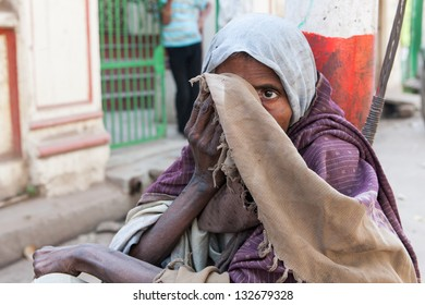 VARANASI,INDIA - MARCH 7:Beggar woman in streets of Varanasi on march 7,2010 in Varanasi,India.The huge amount of Hindu pilgrims that go to Varanasi  attract lots of beggars from all regions in India.