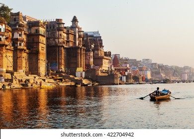 Varanasi,India-March 22,2013:Life along the Ganges (Ganga) River.Pilgrims bath and pray, people walk,washes and dry laundry.Tourists take boat  to sea old temples and ghats from the river.