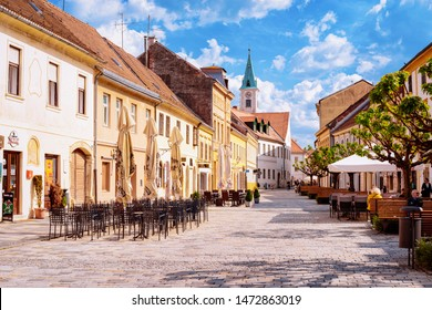 Varazdin, Croatia - May 1, 2019: Street cafes and restaurants and people on benches in Old city of Varazdin in Croatia. Cityscape of famous Croatian town in Europe in summer