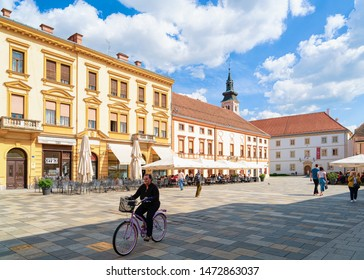 Varazdin, Croatia - May 1, 2019: Senior woman on bicycle at Street cafes and restaurants on Town Hall on King Tomislav Square in Old city of Varazdin in Croatia. Croatian town in Europe in summer