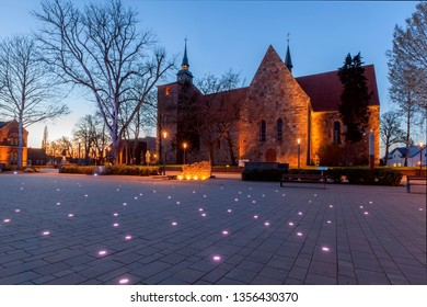 Varel, Germany - April 01, 2019: scenic evening view of the church Schlosskirche (palace church) during blue hour with the beautifully illuminated square Schlossplatz