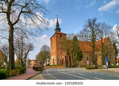 """Varel, Germany - March 30, 2019: the historic church Schlosskirche (""""Palace Church"""") in front of vivid blue sky with white clouds on a sunny day in early spring seen from the street"""