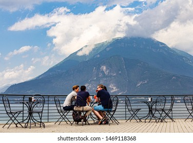 Varenna italy 26.07.2019: European people have a breakfast on terrace cafe of with beautiful view the high mountains and shore lake Como in summer sunny day. Chic restaurant in ancient italian city.
