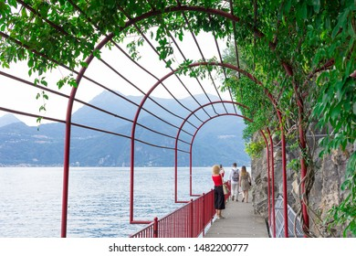 VARENNA, ITALY - AUGUST 17, 2019: The suggestive lakeside promenade of Varenna, built between the rock and the water on the right of the wharf, il called the lovers' promenade