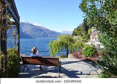 Varenna/Italy - April 9, 2014: Young lady eating an ice-cream sitting on a bench at the lake Como lakefront in a beautiful sunny spring day.