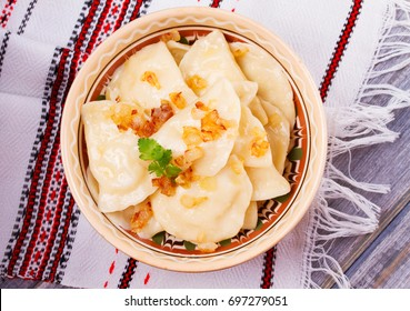 Varenyky, vareniki, pierogi, pyrohy or dumplings, filled with potato and served with salty caramelized onion. View from above, top studio shot, overhead